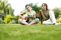 Teenage boy watching his girlfriend playing guitar