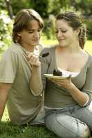 Teenage couple sitting on the field enjoying a piece of cake