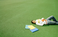 Teenage girl sleeping on the field with books beside her