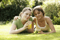 Teenage girls lying forward on the field enjoying their drinks