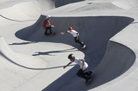 Three teenage boys (16-17) skateboarding at skate park elevated view
