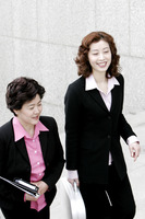 Two career women talking while walking up the stairs