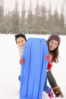 Two girls getting ready to go sled riding