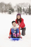 Two girls playing in the snow, riding sled