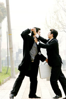 Two men in business suits fighting