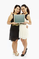 Two women holding up a blank blackboard
