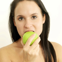 Woman biting on a green apple
