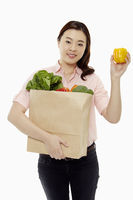 Woman carrying a bag of groceries and holding up a capsicum