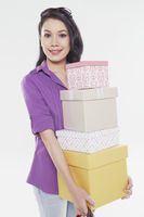 Woman carrying a stack of gift boxes