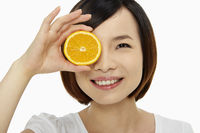 Woman covering one eye with an orange
