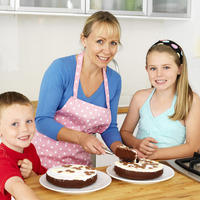 Woman cutting cake, boy and girl smiling at the camera