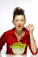 Woman eating a bowl of salad