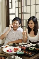Woman eating, man talking on the phone
