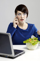 Woman eating salad while talking on the hand phone