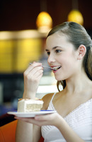 Woman enjoying a piece of cake in the cafe