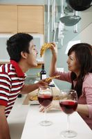 Woman feeding man pizza