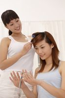 Woman filing her fingernails while her friend styling her hair