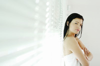 Woman folding her arms while leaning against window blinds