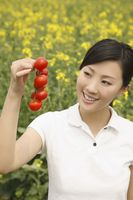 Woman holding a bunch of cherry tomatoes