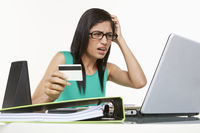Woman holding a credit card, looking frustrated