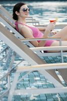 Woman holding a glass of fruit juice while relaxing on lounge chair