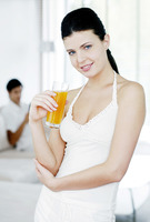 Woman holding a glass of orange juice with her boyfriend sitting in the background