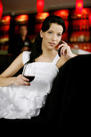 Woman holding a glass of red wine while talking on the phone