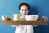 Woman holding a tray of breakfast