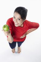 Woman holding an apple while standing on weighing machine