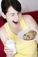 Woman holding cookies and a glass of milk