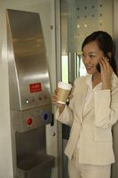 Woman holding cup of coffee while talking on the phone