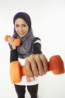 Woman holding out dumbbells