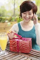 Woman holding ribbon at gift box while talking on the phone