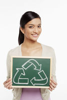 Woman holding up a black board with a recycle symbol on it