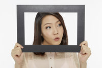 Woman holding up a black picture frame, looking curious