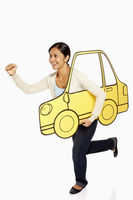 Woman holding up a cardboard car, cheering