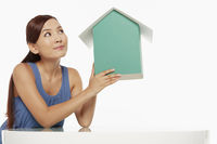 Woman holding up a cardboard house, contemplating