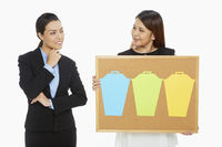 Woman holding up a pin board while the other contemplates