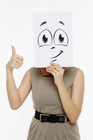 Woman holding up a smiley face doodle