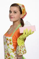 Woman in apron holding cleaning sponge