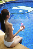 Woman in bikini sitting on the pool side holding a glass of cocktail