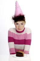 Woman in party hat with a cake on the table