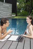 Woman in pool talking to man