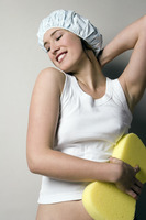 Woman in shower cap scrubbing her body with a bath sponge