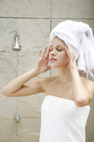 Woman in towel closing her eyes while massaging her own head