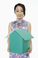 Woman in traditional clothing holding up a cardboard house