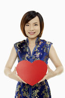 Woman in traditional clothing holding up a red heart