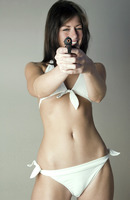Woman in white lingerie pointing a gun at the camera
