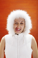 Woman in winter clothing licking her lip