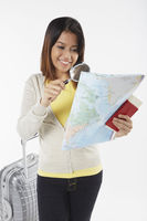 Woman looking at map with magnifying glass